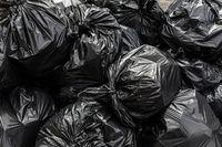 Pile of black waste plastic bin bag background.