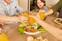 Familie beim Anstoßen mit gesundem Orangensaft