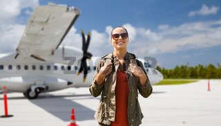 young woman with backpack over plane on airfield