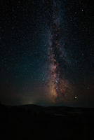 Milky Way and pink light at mountains. Night colorful landscape. Starry sky with hills at summer. Be