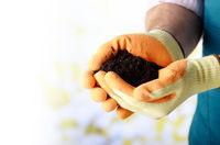 Farmer shows soil in his hands weared in gloves