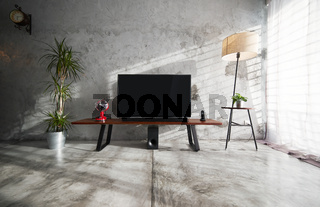Modern living-room interior with TV in a loft style with wooden TV deck and concrete walls and floor . There are vintage fan and clock