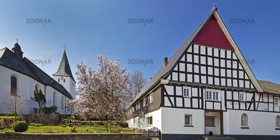 church Mariae Himmelfahrt and half-timbered house, Schoenholthausen, Finnentrop, Germany, Europe