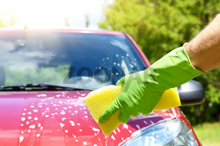 Male hand in green glove with yellow sponge washing car