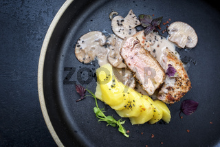 Fried pork fillet with boiled potatoes and cream sauce as top view on a plate with copy space left