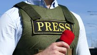 Hand with a microphone on the background of a bulletproof vest with an inscription press