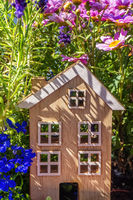 Wooden house between flowers in the green