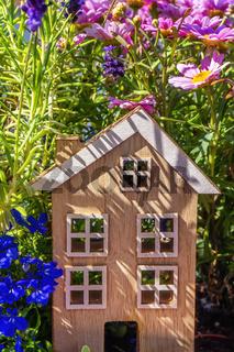 Holzhaus zwischen Blumen im Grünen