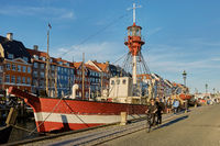 People cycling through colourful facades and restaurants on Nyhavn embankment and old ships along th