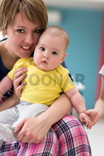 Portrait of young happy mother holding newborn baby boy