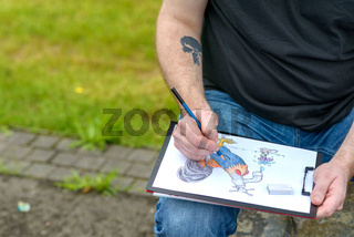Artist in jeans seated outdoors sketching cartoon
