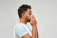 indian man with paper napkin blowing nose