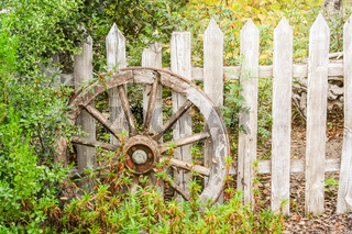 wooden wheel at a wooden fence