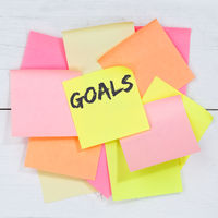 Goal goals to success aspirations and growth business concept desk note paper