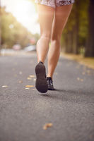 Young woman jogging down an autumn street