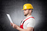 Surprised construction worker holding papers