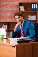 Young handsome employee sitting in the office