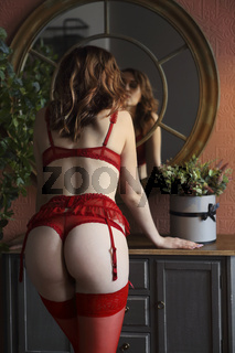 Young woman with bright hair in red lingerie by the mirror