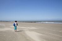 Woman on deserted sandy beach at Cadzand