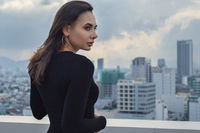 Outdoor portrait of young beautiful woman on rooftop with city view at rainy moody day