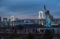 TOKYO, JAPAN - 21 FEB 2018: Tourists enjoying view of japanese statue of liberty and rainbow bridge at blue hour