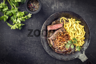 Traditional dry aged sliced roast beef with fried onion rings and Swabian spaetzle as top view in a wrough-iron pan with brown sauce