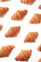 Food pattern with french homemade croissants on a white background.