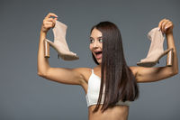 Beautiful young Woman holding heels shoes