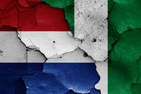 flags of Netherlands and Nigeria painted on cracked wall