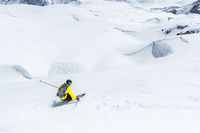 A skier at speed rides on a snowy slope freeride. The concept of winter extreme sports