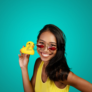 Bright summer portrait of beautiful smiling woman with yellow rubber duck over bright blue screen background