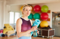 Junge Frau als Fitnesstrainer im Sportstudio