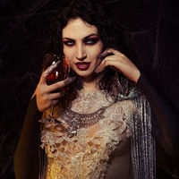 Vampire Halloween Woman portrait. Beauty Sexy Vampire Girl with drinking blood on her glass of wine. Vampire makeup Fashion Art design. Attractive model girl in Halloween costume and make up