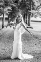 Full length portrait of beautiful sensual young blond bride in long white wedding dress and veil, holding bouquet outdoors in natural background.
