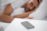 smartphone on bedside table near sleeping man