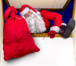 Santa Claus carrying a bag through a window