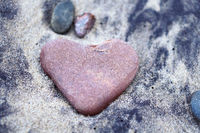 sea stone in the shape of a heart on the sand, red stone heart