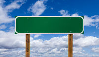 Blank Green Road Sign with Wooden Posts Over Blue Sky and Clouds