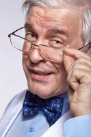 Close up portrait of senior businessman clerk with glasses looking ironically at the camera