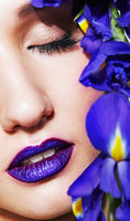 Portrait of young beauty female face with violet lips makeup and irist flowers near face