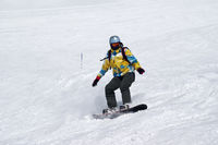 Snowboarder descends on snowy ski slope at high winter mountains
