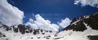 Panoramic view on snowy sunlit mountains and blue cloudy sky