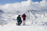 Little skier with father on top of snowy ski slope