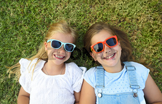 Laughing children wearing sunglasses relaxing during summer day