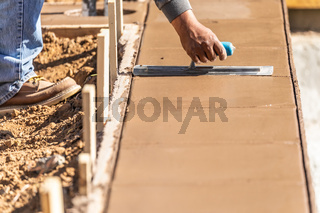 Construction Worker Using Trowel On Wet Cement Forming Coping Around New Pool