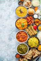 Composition of Indian cuisine in ceramic bowls on stone table