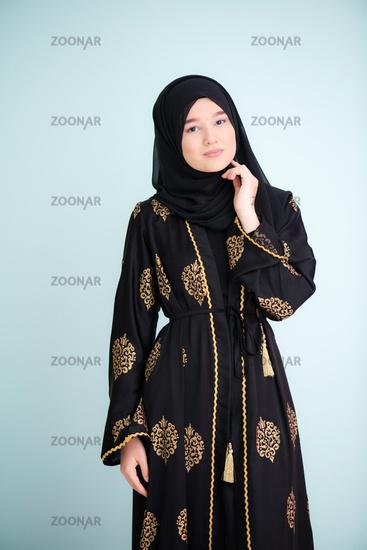 muslim woman with hijab on cyan backgrund