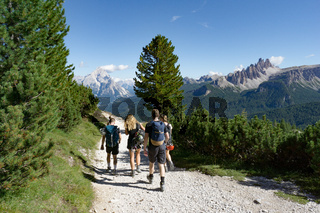 climbers walking down a road in a Dolomite mountain landscape after a hard climb