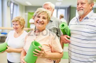 Glückliche Senior Frau mit Freunden im Fitnessstudio