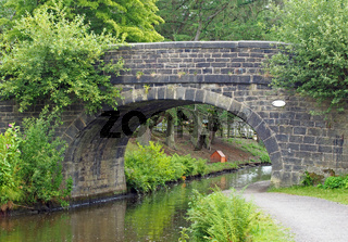 an old stone bridge crossing the rochdale canal at mytholmroyd west yorkshire with a waterside pathway surrounded by trees and bushes